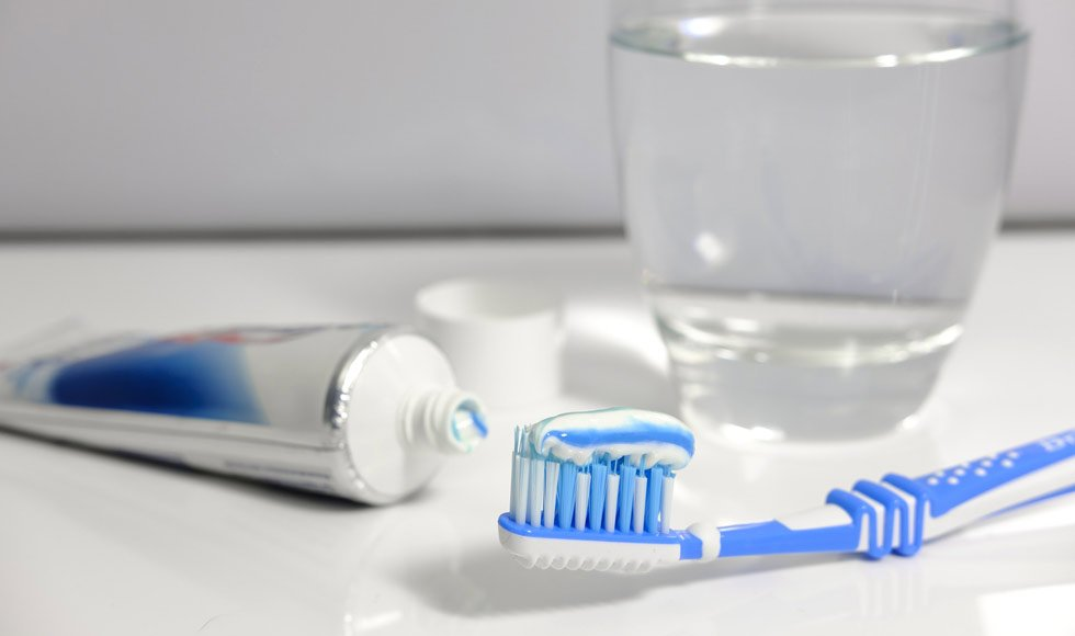 toothpaste on toothbrush on bathroom counter