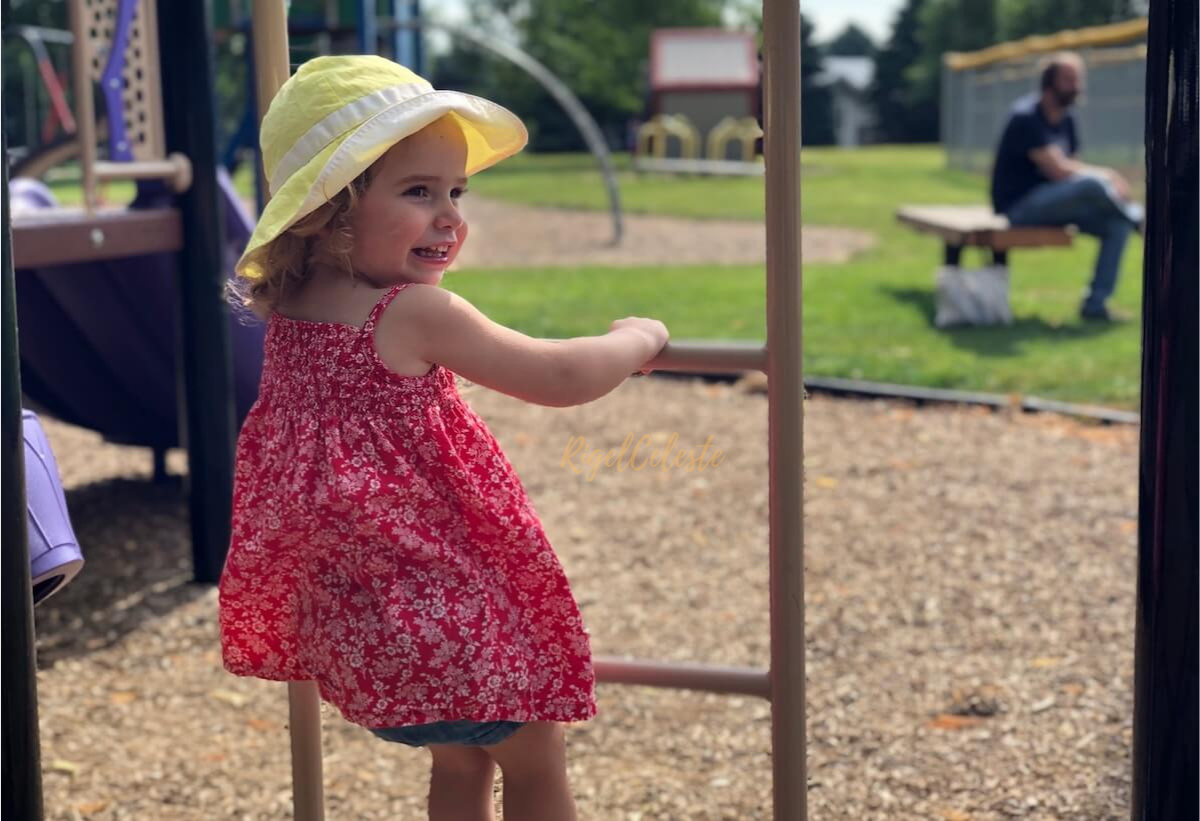 toddler girl in red dress and yellow hat smiling outside