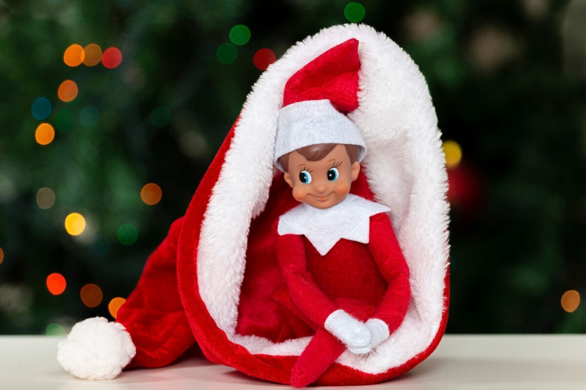 Elf on the shelf sitting and looking curious inside a christmas hat