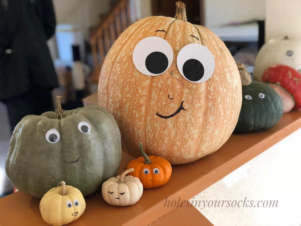 Row of no-carve pumpkins with googley eyes and sharpie marker faces