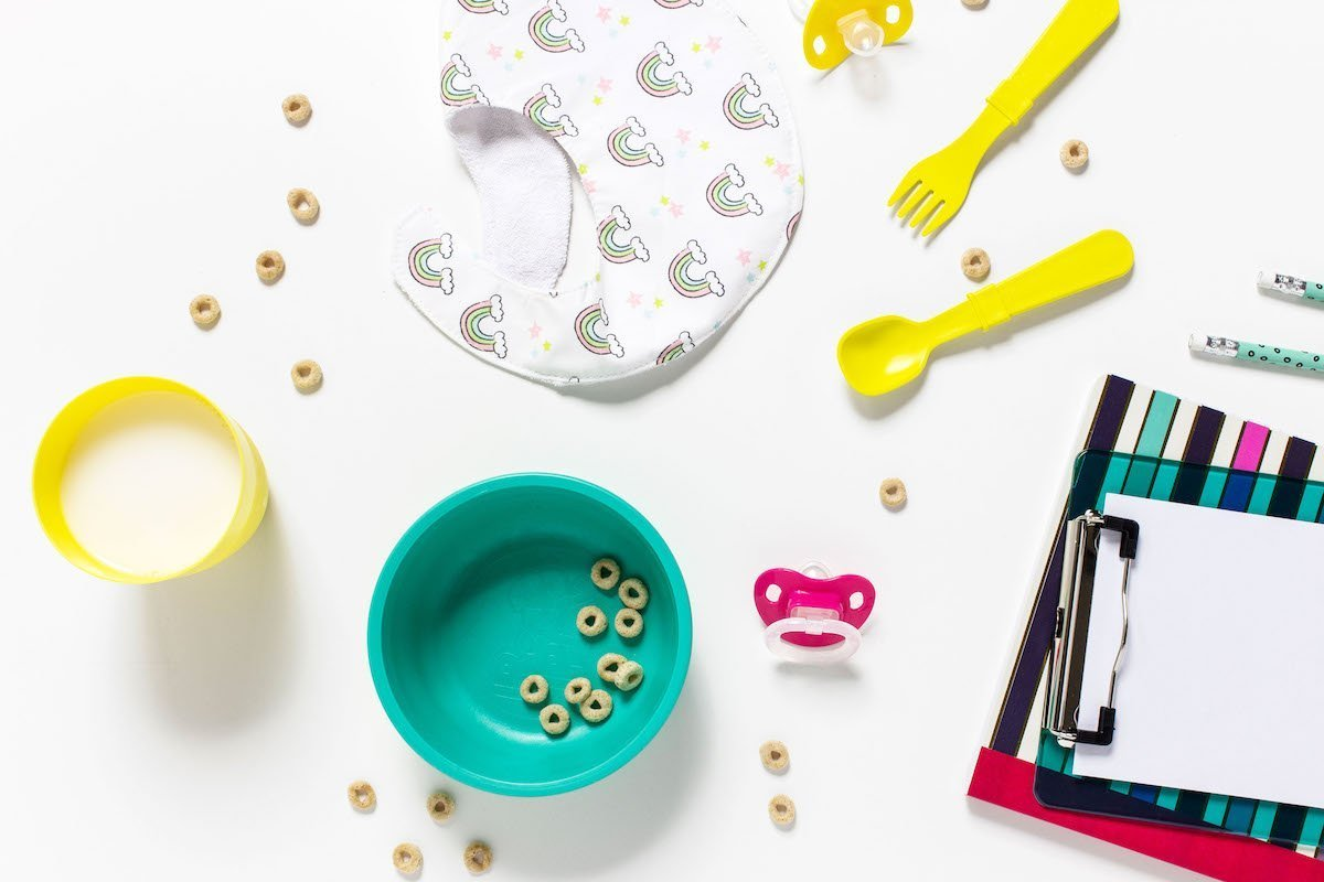 flatlay of partially empty cereal bowl, bib, plastic utensils -- morning routine on school days