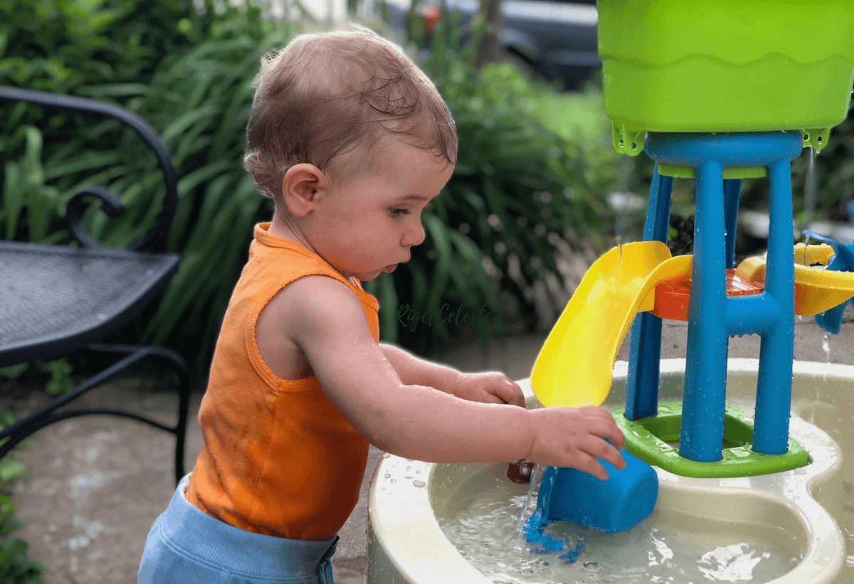 toddler playing outside in water table